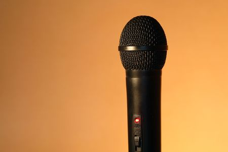 shure: A modern black handheld ball head microphone on ginger background with copy space