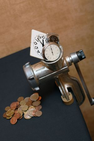 Conceptual still life with mincing machine, coins and clock photo