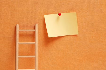 Conceptual background with wooden ladder against ginger wall and hanging blank note pad Stock Photo - 7597660