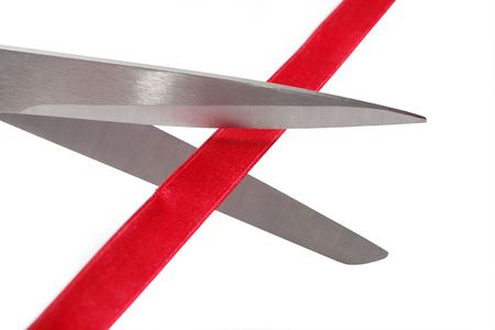 Closeup of sciccors cutting the red band on white background photo