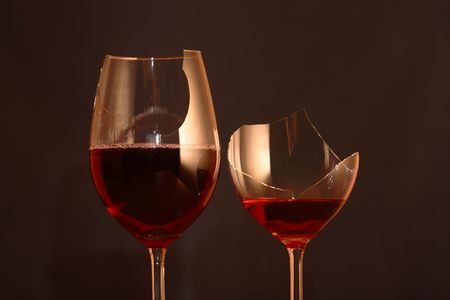 Two broken goblets with red wine on dark background photo