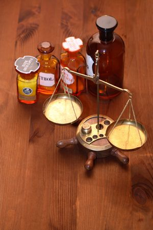 Set of ancient glass pharmaceutical phials near brass weight scale on wooden background