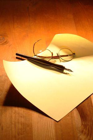 pluma de escribir antigua: Espect�culos antiguos y pluma de tinta acostado de hoja en blanco sobre fondo de madera  Foto de archivo