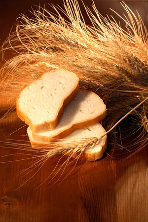 Still life with white sliced bread and ears of wheat on wooden background Stock Photo - 7883405