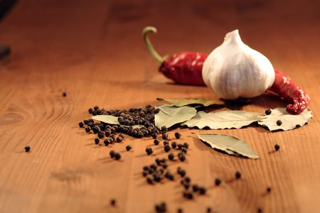 Bay leaves, head of garlic and peppercorns on wooden background photo