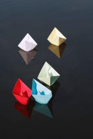 multy: Set of motley paper boats on water background.