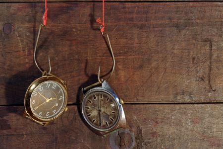 Two old watches hanging on fish hooks on wooden background photo