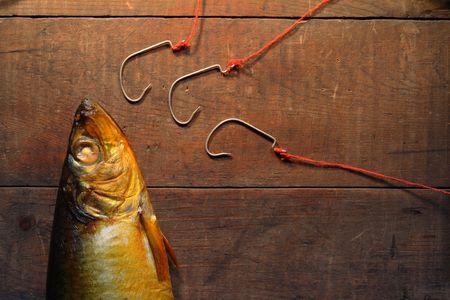 Closeup of bloater near three fishing hooks on wooden background photo