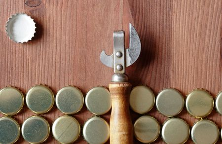 bottle cap opener: Old opener between lot of bottle caps on wooden background Stock Photo