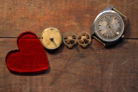 Red glass heart near gears and old watch on wooden background