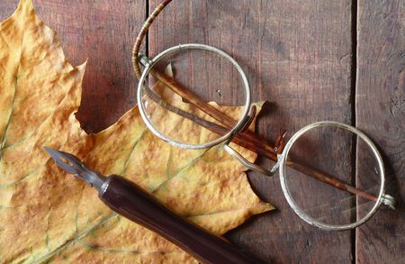Vintage still life with dry maple leaf, ink pen and old spectacles lying on wooden background photo