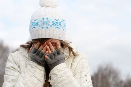 Nice young girl hide face behind her fingers photo