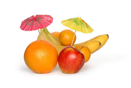 multy: Orange and apple with small paper sunshades and other fruits on white background. Clipping path is included