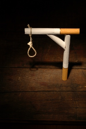 gibbet: Gibbet made from cigarettes and rope on dark wooden background