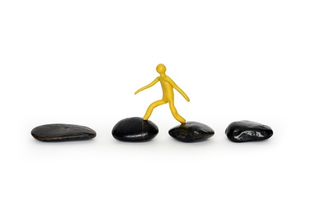 adroitness: Yellow plasticine man walking on black stones. Isolated on white