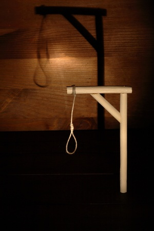 capital punishment: Gibbet with loop on gloomy wooden background Stock Photo