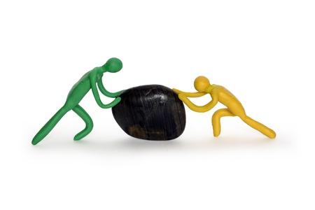 sisyphus: Two plasticine men pushing black stone. Isolated on white