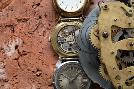 Closeup of old brass clock mechanism and watches on red brick background with copy space photo