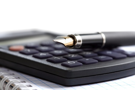 Fountain pen lying on calculator and spiral notebook isolated on white background photo