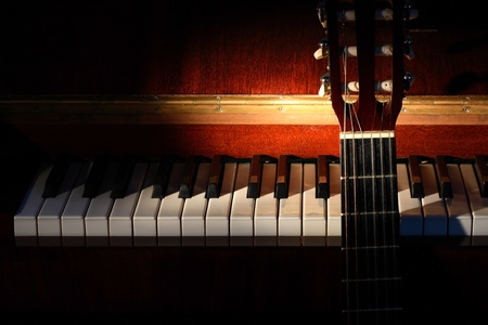 classical guitar: Closeup of guitar standing near open piano on dark background with lighting effect Stock Photo