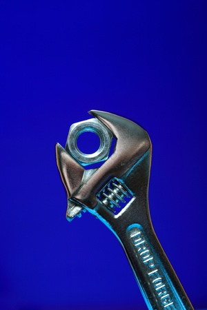 Extreme closeup of adjustable wrench gripping a screw nut on blue background photo