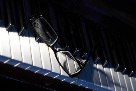 Closeup of black eyeglasses lying on piano keys. Black copy spase for your text Stock Photo - 8508757