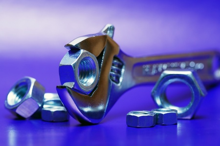 Extreme closeup of adjustable wrench gripping a screw nut on blue background with nuts photo