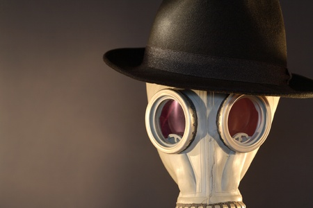 Gas mask with a felt hat closeup on dark background Stock Photo - 8665235