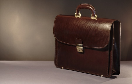 cuir marron: New brown leather briefcase on dark background with copy space Banque d'images