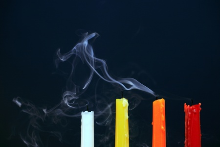 multy: Four color extinguished  candles with smoke on black background Stock Photo