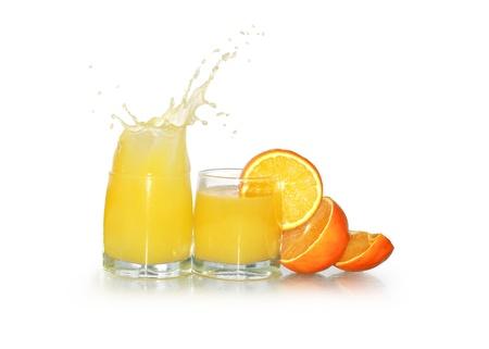 Two glasses of splashing orange juice and fruits isolated on white background Stock Photo - 8737886