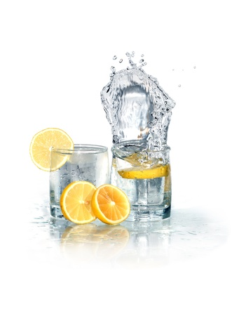 Two glasses of splashing water with ice and lemon. Isolated on white  photo