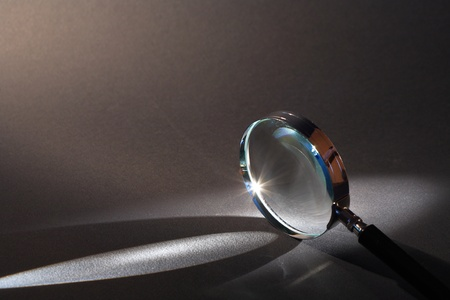 magnifying glass: Closeup of magnifying glass standing on dark surface with beam of light