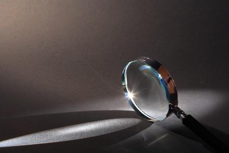lupa: Detalle de lupa permanente en superficie oscura con haz de luz