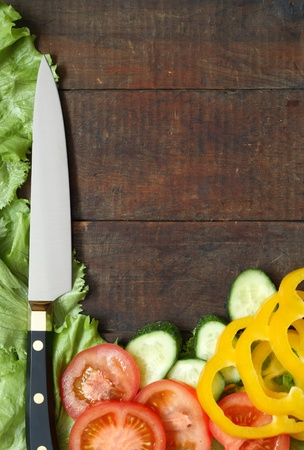 Kitchen knife and sliced vegetables lying on wooden surface with copy space