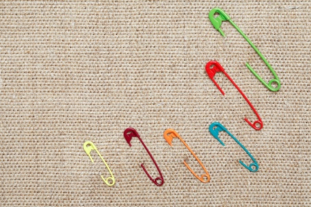 multy: Few color safety pins attached to canvas background