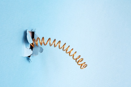 Metal spring jump out through a blue disrupt paper background Stock Photo - 9014672