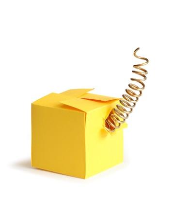 metal spring: Metal spring inside closed yellow paper box.