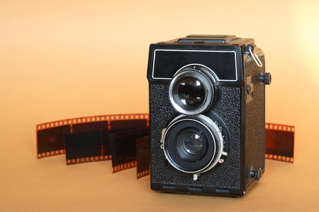 Vintage twin lens camera near film isolated on nice yellow background photo