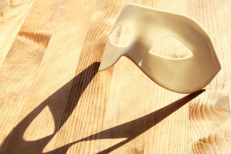 White plastic venetian mask lying on wooden surface with sunbeam and shadow photo