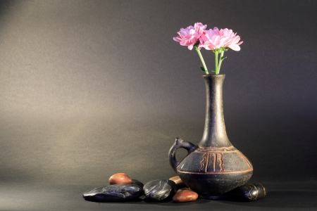Ancient ceramic vase with nice pink flower near stones on dark background