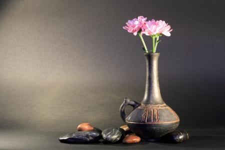 Ancient ceramic vase with nice pink flower near stones on dark background