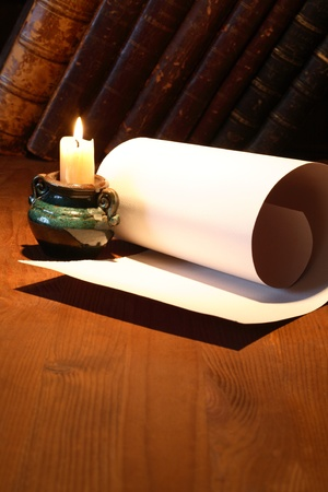 Old paper near lighting candle and stack of vintage books on wooden surface photo