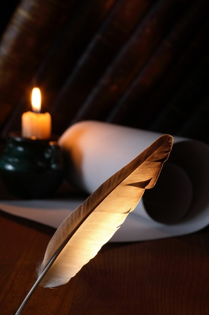Closeup of quill pen standing on dark background with lighting candle and scroll