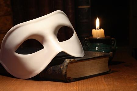 teatro antiguo: Detalle de m�scara blanca veneciano acostado cosecha libro antiguo cerca de vela de iluminaci�n Foto de archivo