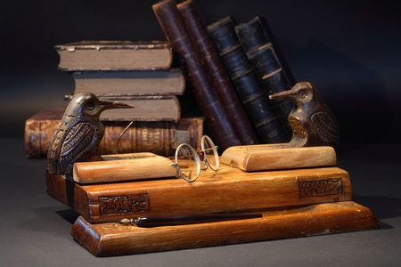 Nice old vintage wooden desk set near old books on dark background photo