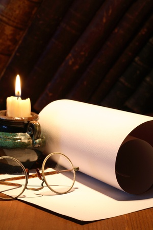 Scroll and old spectacles near lighting candle on dark background with vintage books photo