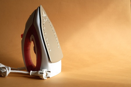 Modern electric iron standing on nice gold background with sun lighting photo