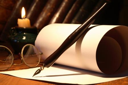 スクロールと古い眼鏡と木製の表面に照明蝋燭の近くのインクのペン 写真素材