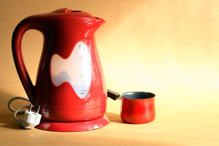 electric kettle: Modern red electric kettle and coffeepot standing on nice yellow background